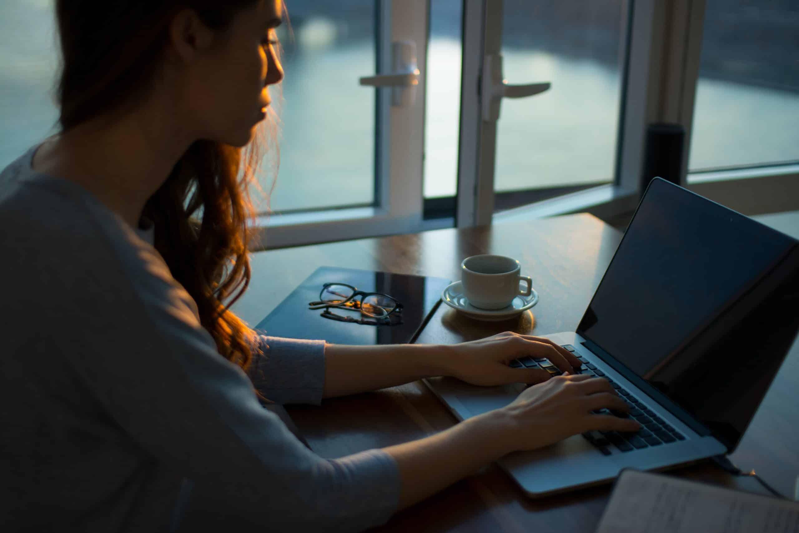 woman sitting beside table using laptop